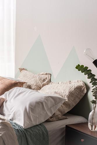 Mit Dreiecken bemalte Wand hinter dem Bett mit verschiedenen Kissen