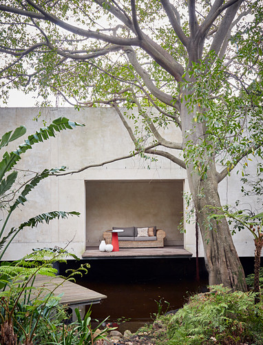 Blick vom naturnahen Garten auf ein Betonhaus mit Sofa in der Loggia
