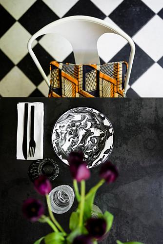 Blick von oben auf schwarzen Tisch mit marmoriertem Teller