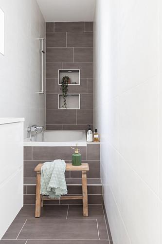 Bathtub in narrow bathroom with light grey tiles on floor and back wall