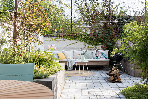 Cushions on bench and barbecue in courtyard garden