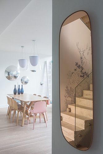 Staircase reflected in oval mirror and modern dining table in background