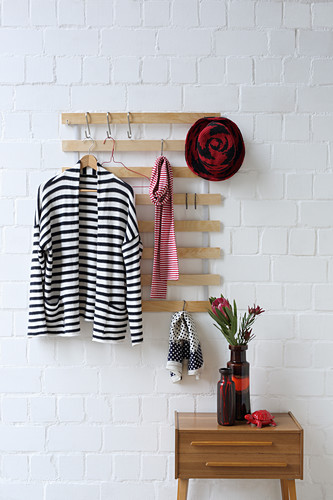 Coat rack made from old bed slats on brick wall