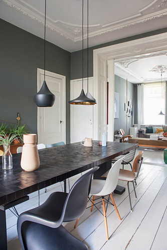 Long dining table and classic chairs in dining room with dark wall and white wooden floor