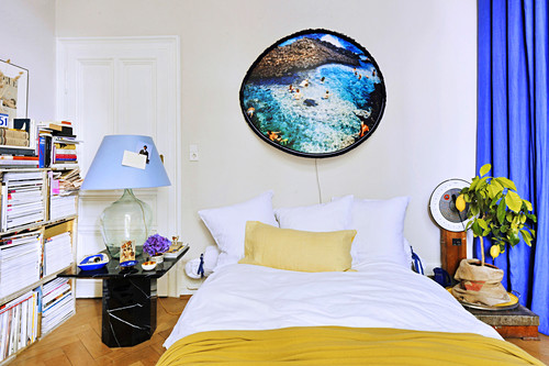 Picture with fluffy frame above bed, potted lemon tree, bedside lamp made from demijohn and open bookshelves in bedroom