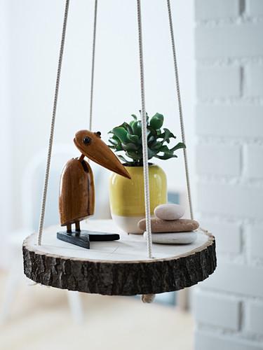 A bird figure, a house plant and stones on a homemade hanging shelf