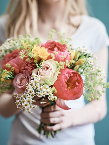 Frau hält Blumenstrauss aus Rosen, Pfingstrosen, Fresien und Kamillenblüten