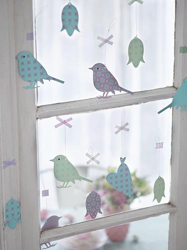 Easter arrangement of metal pendants in window (birds, flowers, hearts)