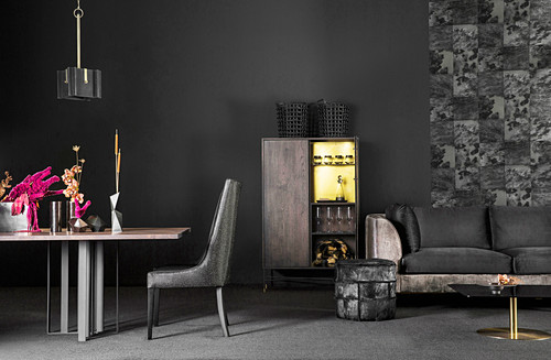 Back velvet sofa, stool, cabinet and dining table and chair in front of black wall