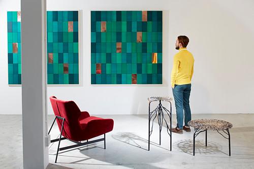 Mann betrachtet Bilder vor kunstvollen Möbeln