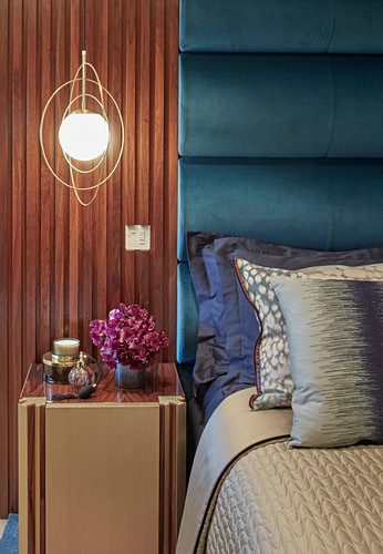 Pendant lamps in golden rings above bedside cabinet next to bed