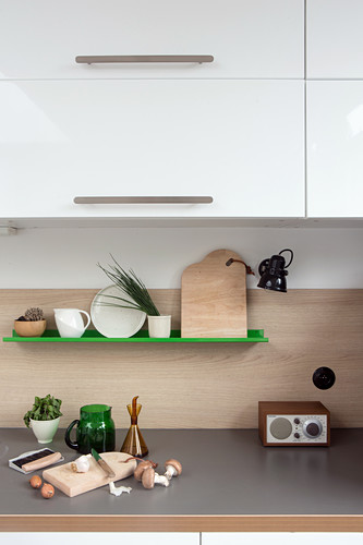 Chopping board on grey worksurface below green shelf and wall units in kitchen