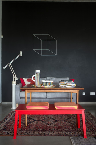 Rote Bank, Holztisch und Sofa vor Tafelwand
