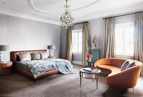 Halbrundes, cognacfarbenes Sofa im Schlafzimmer mit Lederbett