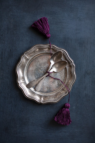 Vintage cutlery with hand-made tassels on pewter plate