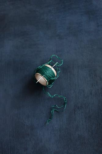 Needle stuck in thread wrapped around cardboard tube