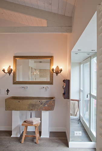 Rustic trough used as washstand in minimalist bathroom