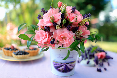 Bouquet of roses in small bucket decorated with transfer