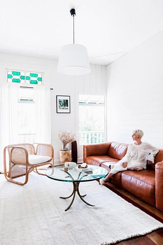 Blonde Frau auf cognacfarbener Ledercouch, Couchtisch mit Glasplatte und Designer-Rattanstuhl im Wohnzimmer mit weißen Wänden