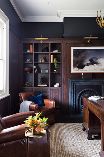 Fireplace, shelf and leather armchairs in the living room with black walls