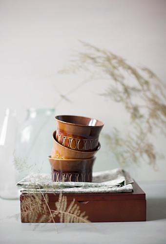 Stapel brauner Retro-Schälchen auf einem Tuch und Holzkästchen