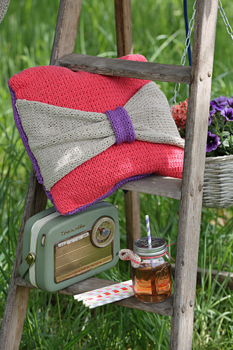 Crocheted cushion with bow and retro radio on ladder