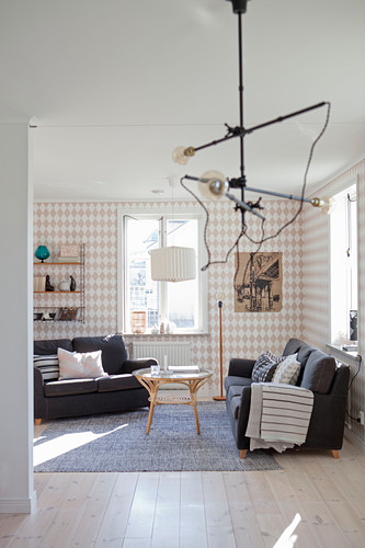 Industrial lamp in front of living room with diamond-patterned wallpaper