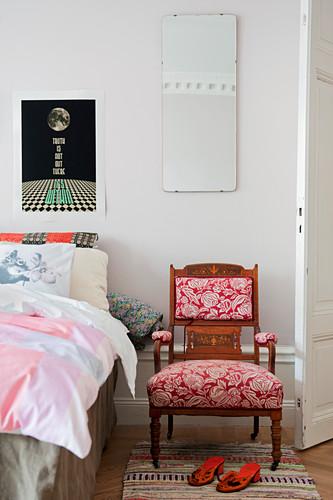 Antiker Stuhl mit geblümtem Polster neben dem Bett