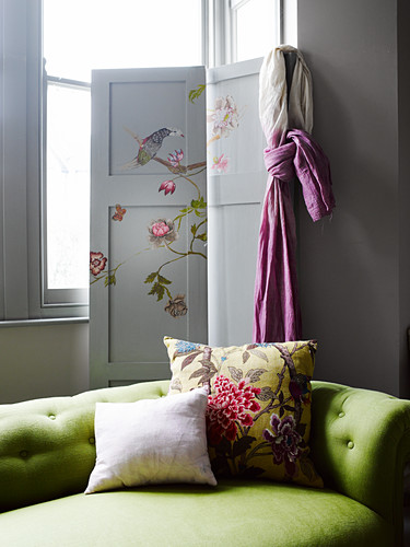 Green sofa in front of screen painted with birds and flowers