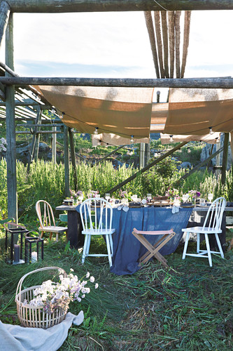 Table set for summer party below wooden frame covered with fabric awnings