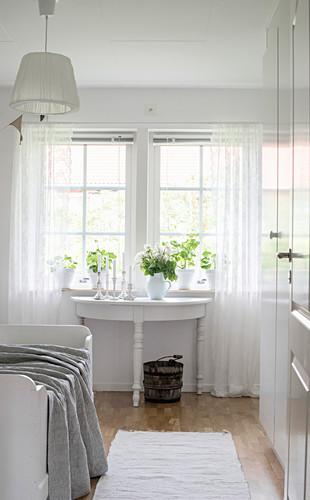 Halbrunder Tisch am Fenster im Schlafzimmer ganz in Weiß