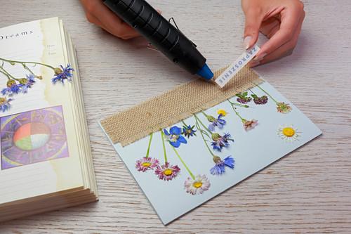 Postkarte mit gepressten Blumen und fransigem Jutestoff