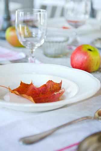 Weißer Teller mit rotem Herbstblatt auf dem gedeckten Tisch mit Äpfeln