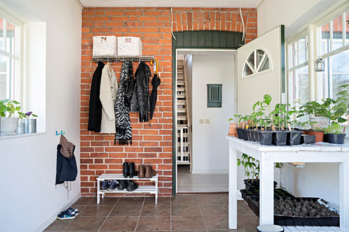 Brick wall and potting table in rustic foyer