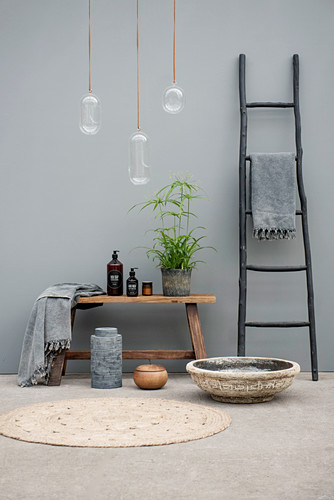 Black ladder and bathroom utensils on wooden bench against grey wall
