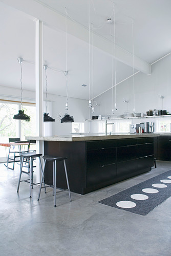 Black cabinets and concrete floor in large kitchen below exposed roof structure