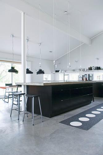 Große Küche mit schwarzen Fronten und Betonboden unter offenem Dach