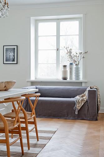 Designerstühle am Esstisch vor dem Sofa mit grauem Überzug