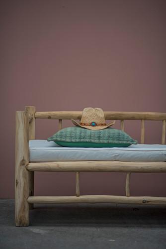 Cowboyhut und Kissen auf rustikaler Holzbank vor rosafarbener Wand