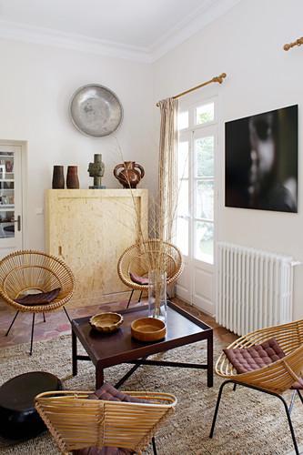 Runde Korbstühle um niedrigen Tisch im mediterranen Wohnzimmer