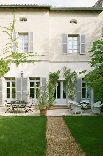 Kiesweg durch gepflegten Rasen zum mediterranen Haus mit Terrasse