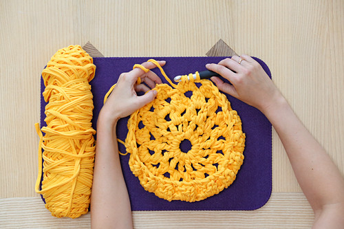 Hands crocheting with yellow jersey yarn