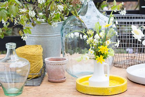Bouquet of narcissus in jug, demijohns, twine, plant pot and zinc bucket on garden table