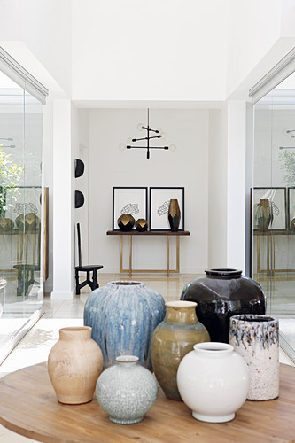 Ceramic vases on table in front of artworks on console table in foyer