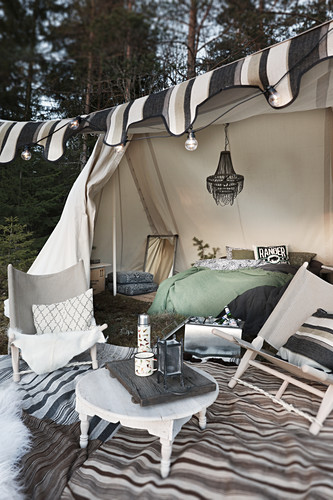 Camp chairs and round table on rug outside furnished tent decorated with fairy lights