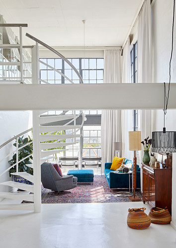 Blue and grey upholstered seating and spiral staircase in double-height, open-plan interior