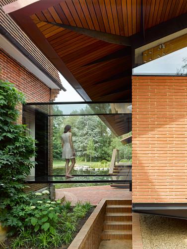 Frau steht im gläsernen Durchgang zwischen zwei Häusern