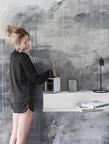 Young woman wearing polka-dot pyjamas in front of grey mural on wall