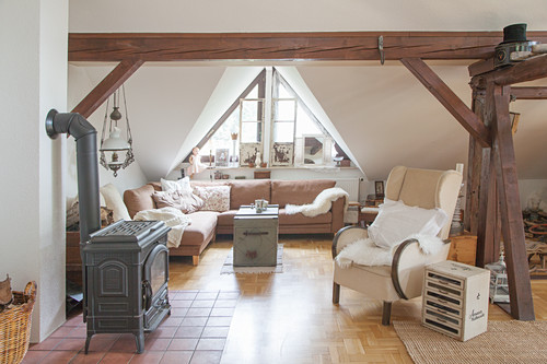 Log burner, wing back chair and corner sofa in cosy living room with wooden beams