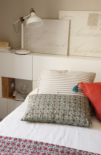 Various cushions on bed and pictures on headboard
